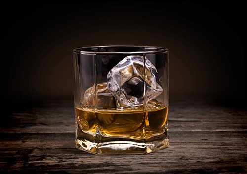 Glass of whisky on ice served on a rustic wooden counter in a pub, bar or restaurant against a dark background with copyspace conceptual of nightlife, relaxation and entertaining